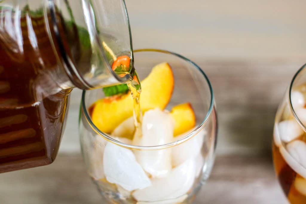 iced tea being poured into glass filled with ice and peaches