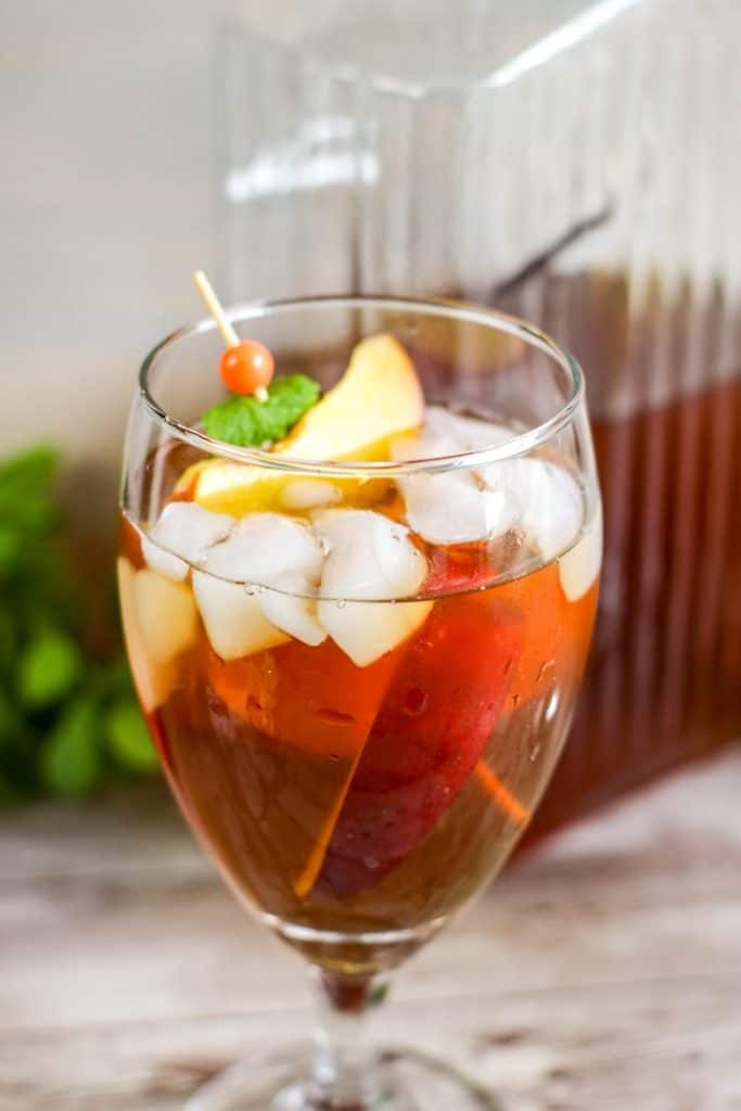 one stemmed glass filled with peaches and iced tea with peach in foreground and glass picture of tea in background