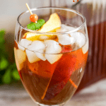 one stemmed glass filled with peaches and iced tea with peach in foreground and glass picture of tea in background with pinterest text overlay