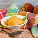 peach sorbet in white bowl on peach colored mat with spoon in front along with plaid napkin in back and two fresh peaches