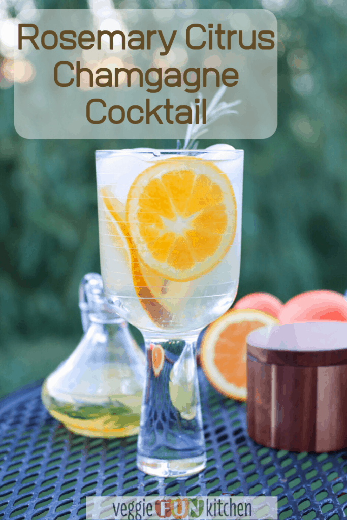 cirtrus champagne in stemmed glass with oranges in background and pinterest text overlay