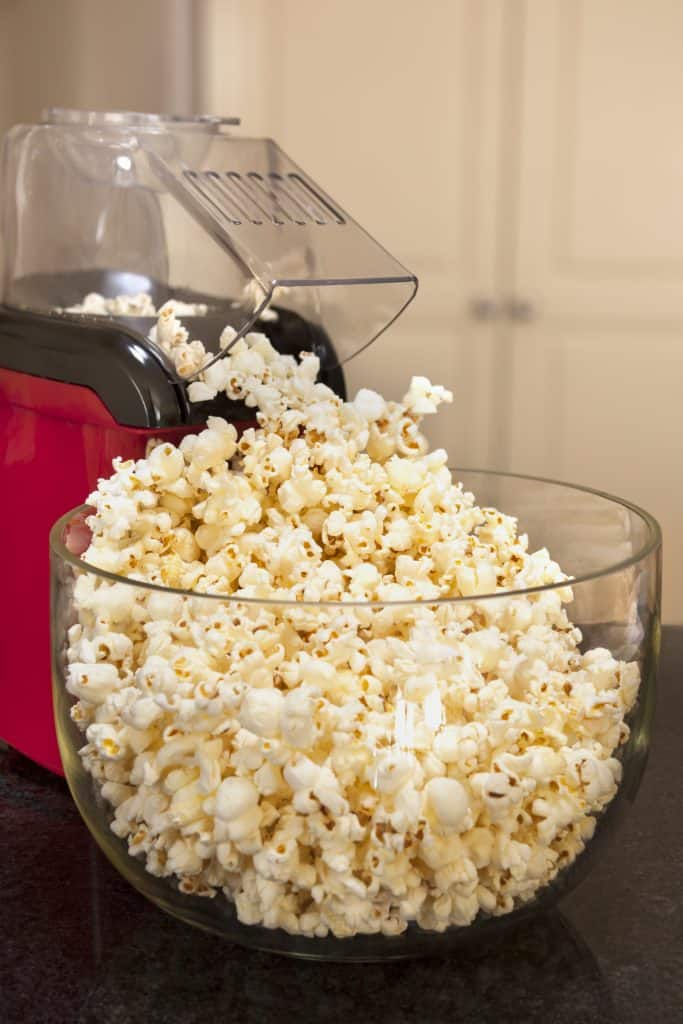 red air popper popping popcorn into clear glass bowl