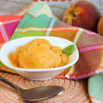 peach sorbet in white bowl on peach colored mat with spoon in front along with plaid napkin in back and two fresh peaches with pinterest text overlay