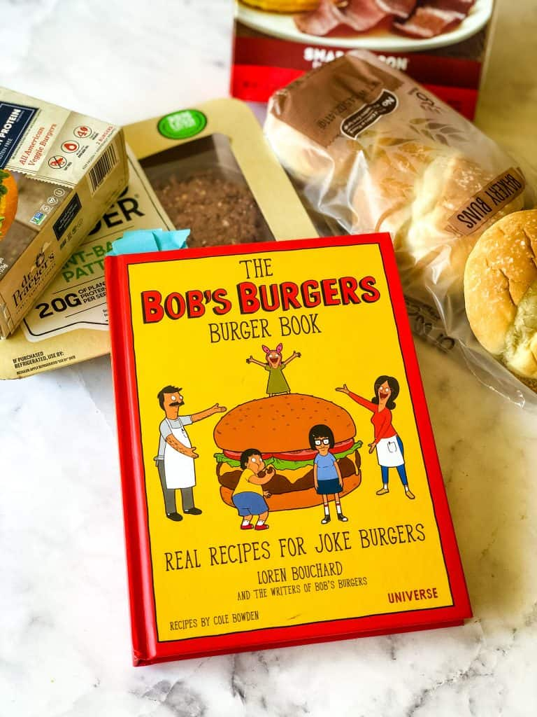 vegan friendly ingredients for hawaiian burger including vegan burgers, bacon, and buns with Bob's Burgers book in foreground