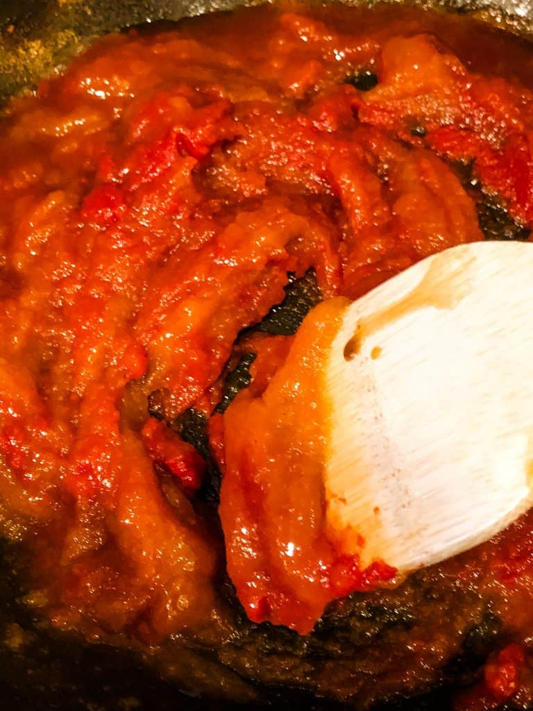 guava bbq sauce cooking in pan stirred with wooden spoon