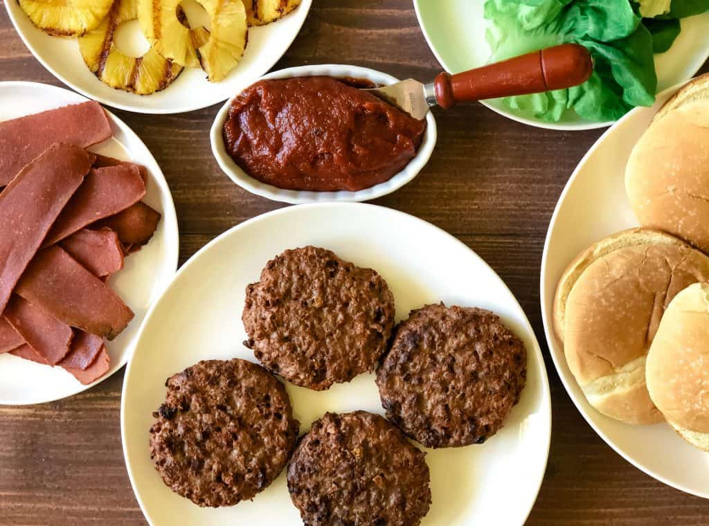 everything needed to build your Hawaiian burger including vegan bacon, grilled pineapple, guava bbq sauce, vegan burgers, buns, and lettuce