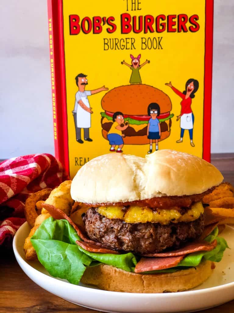 Hawaiian burger on plate with fries in background with Bob's Burgers book