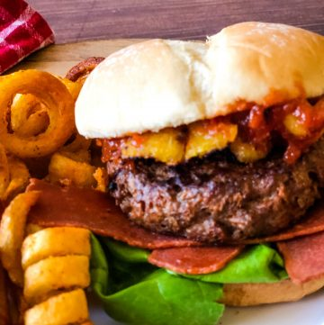 Hawaiian burger on plate with fries in background