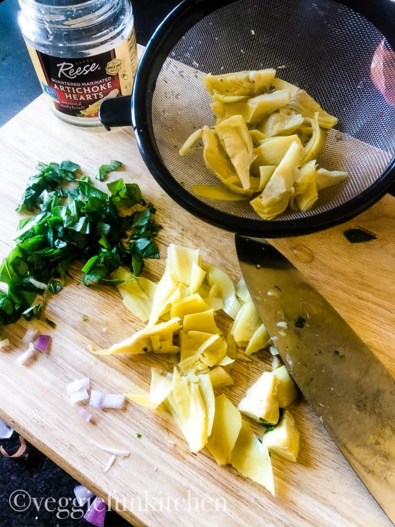 chopped artichoke hearts and basil with a few onions on cutting board with artichokes in mesh strainer