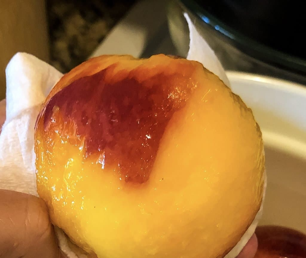 mostly peeled peach in hand