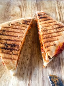 two pizza panini halves on wooden cutting board