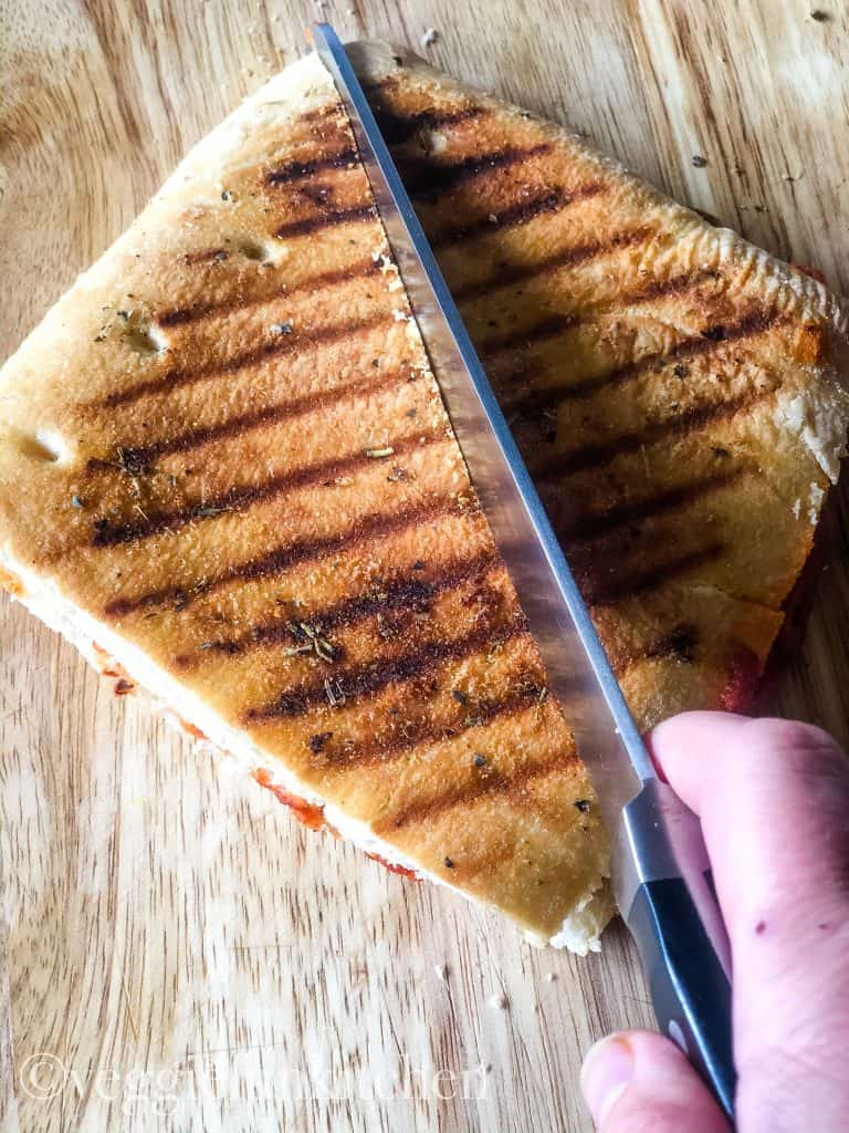 pizza panini sandwich being cut in half with knife