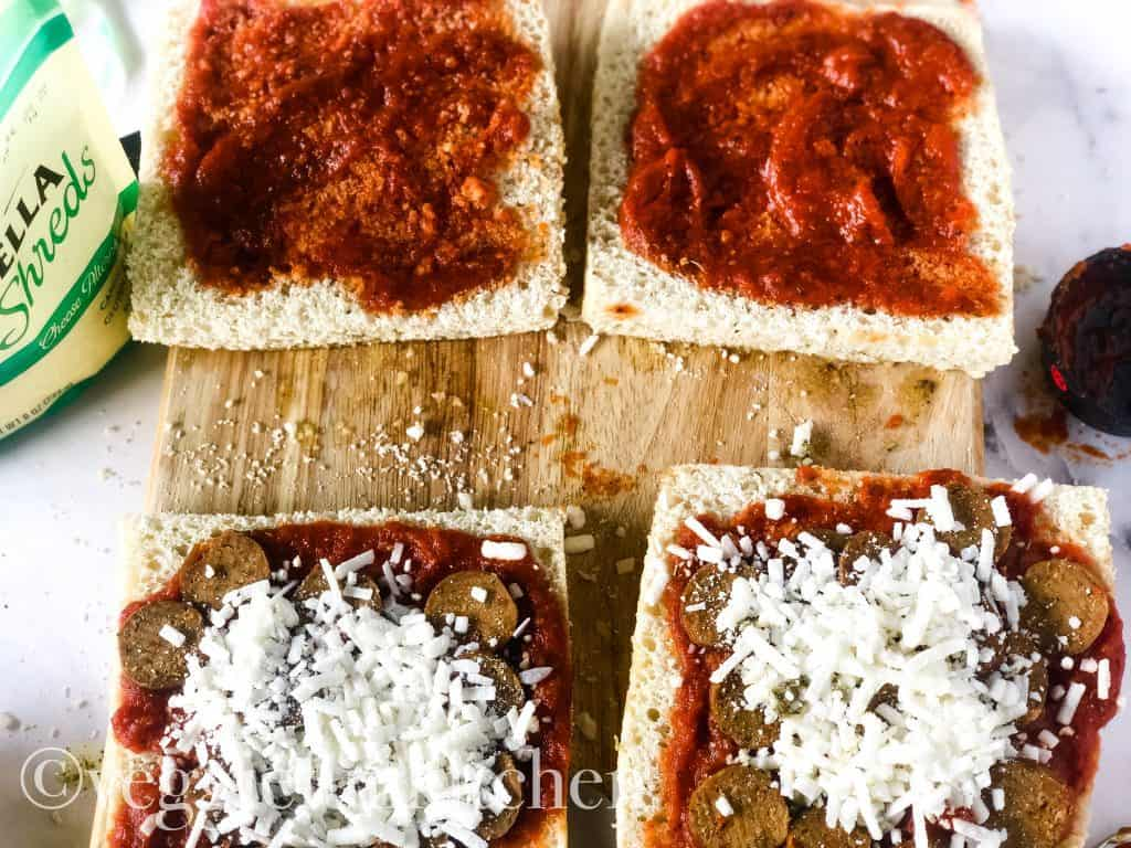 two pizza panini sandwiches being put together with sauce, cheese, and sausage