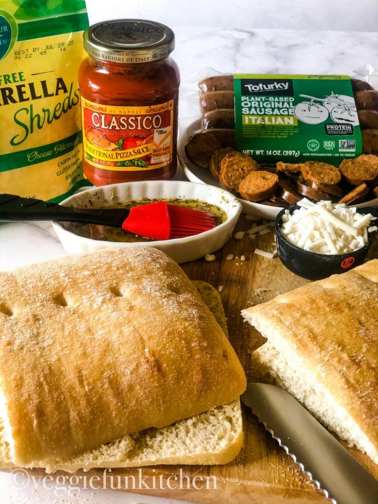 ingredients for pizza panini including bread, vegan cheese and sausage, and sauce