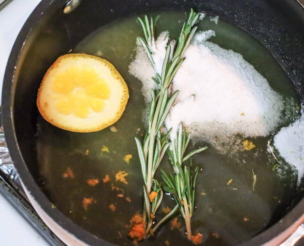 making simple syrup with oranges rosemary and sugar in dark pan