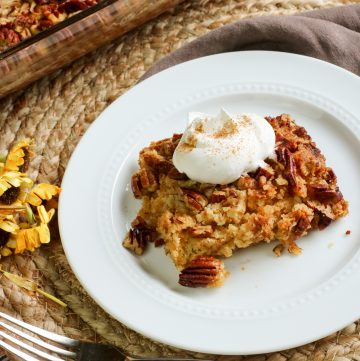pumpkin dump cake with coconut whipped topping on white plate with cake in glass pan in background