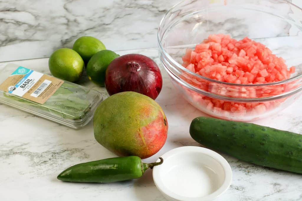 ingredients for watermelon salsa including limes, basil, mango, red onion, cucumber watermelon