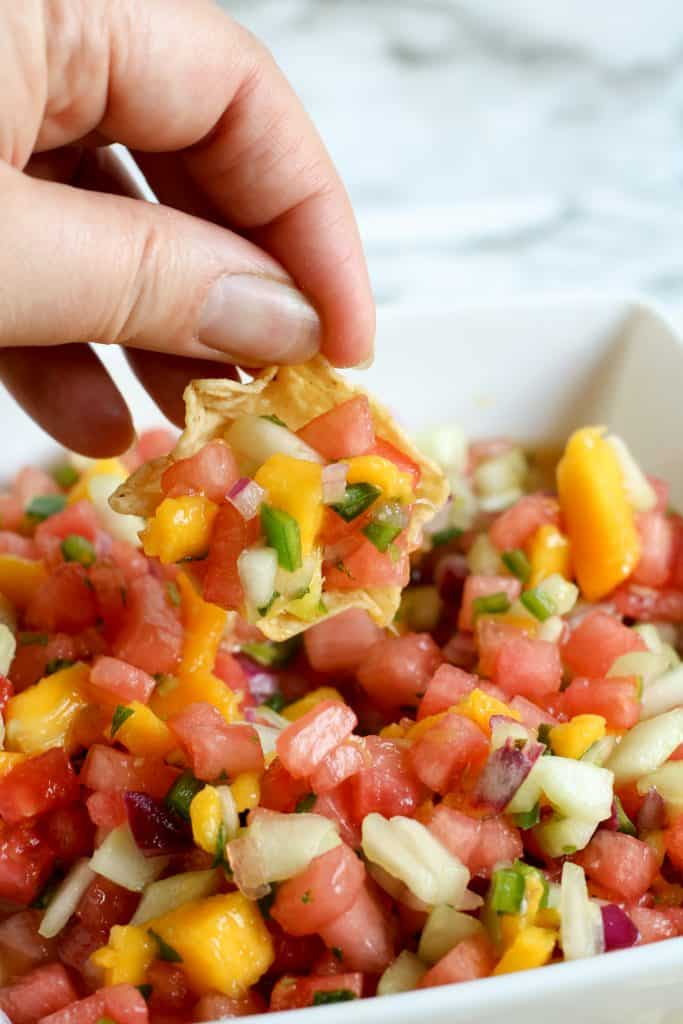 hand holding chip with watermelon mango salsa