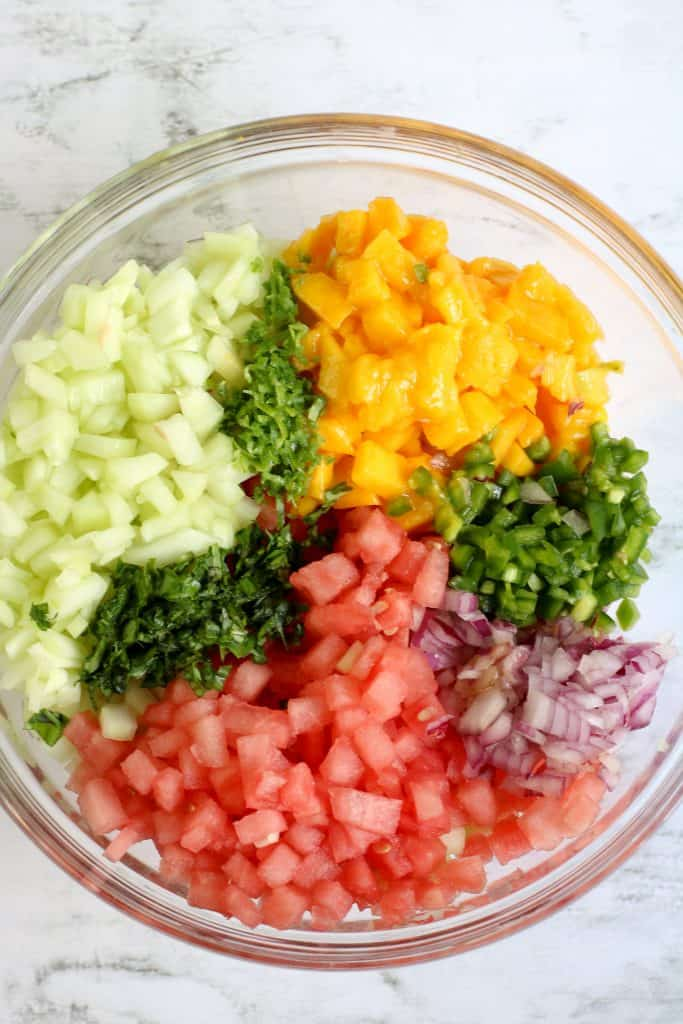ingredients for watermelon mango salsa including diced cucumbers, basil,mango, jalapeno, red onions, watermelon in glass bowl