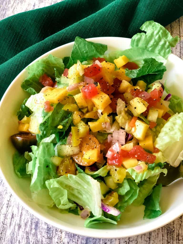 salad on white plate topped with fruit salsa with green napkin in background