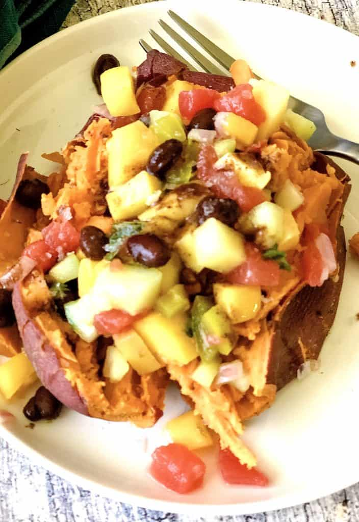 sweet potato topped with fruit salsa on white plate with fork