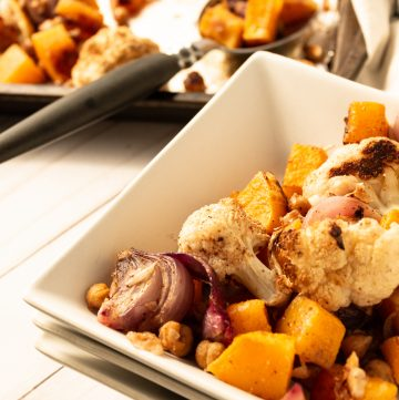 roasted butternut squash and cauliflower in white square dishes with sheet pan in background