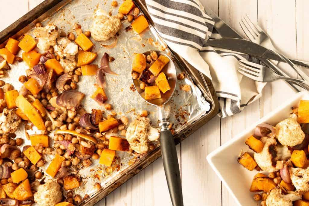 roasted butternut squash and cauliflower in white square dishes with sheet pan and roasted veggies
