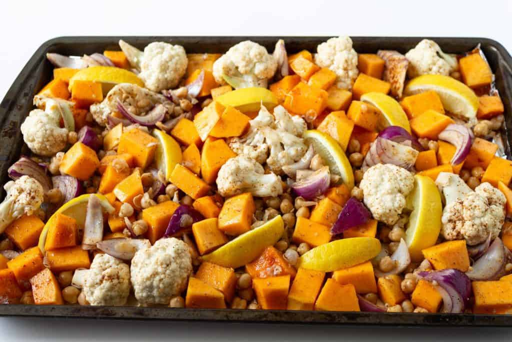 sheet pan with seasoned butternut squash and cauliflower ready to be roasted