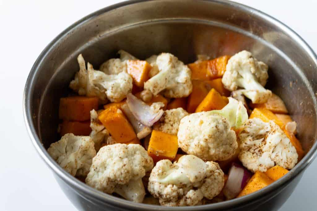 cauliflower, onions, chickpeas, butternut squash all in a metal bowl tossed with seasonings