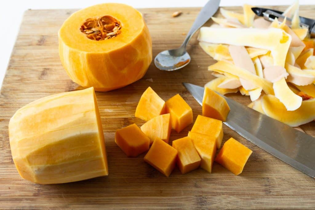 peeled butternut squash being cut