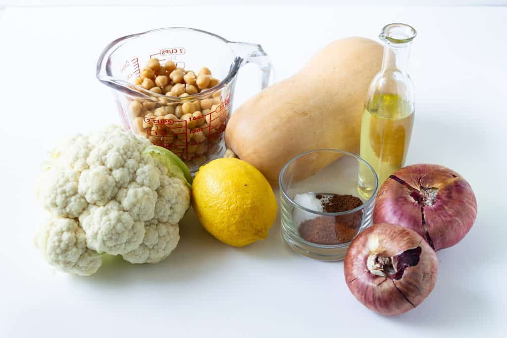 ingredients needed for sheet pan meal including head of cauliflower, chickpeas in a measuring cup, lemon, butternut squash, oil oil, spices, and red onions.