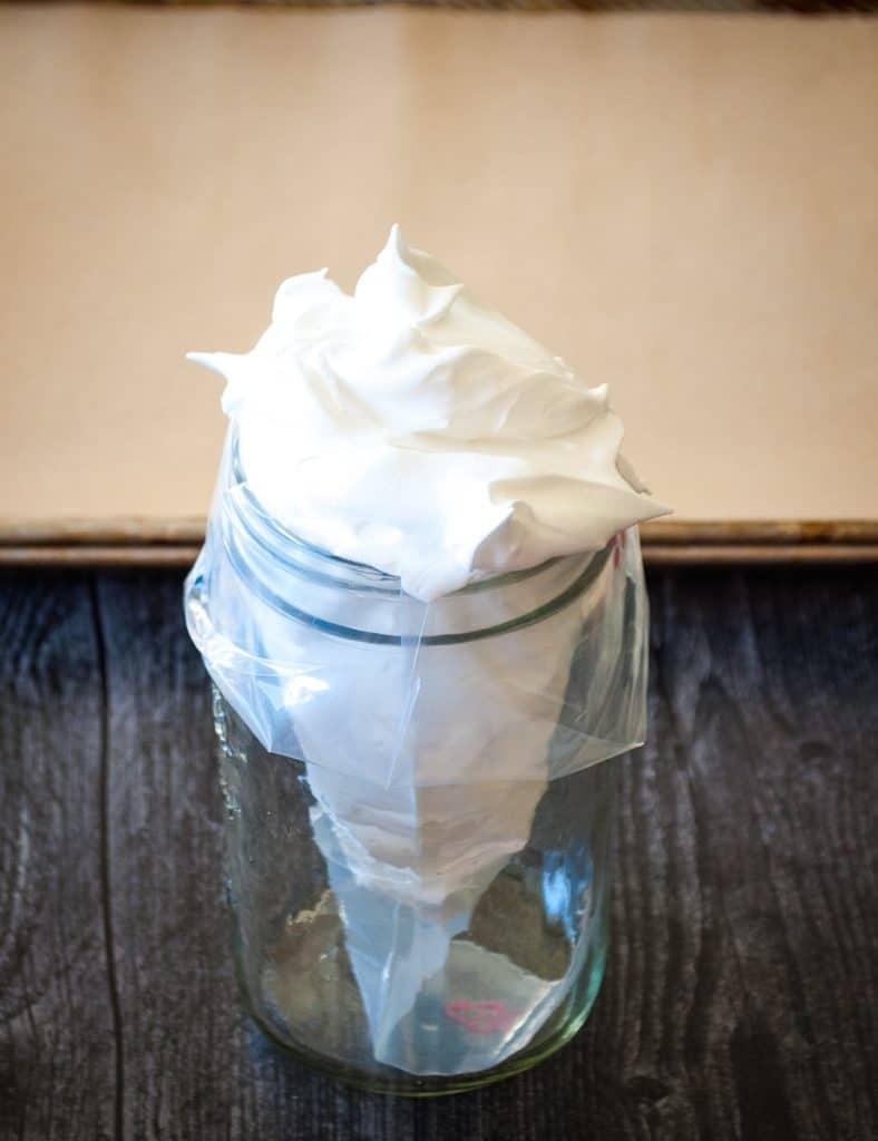 aquafaba meringue in clear pastry bag in jar