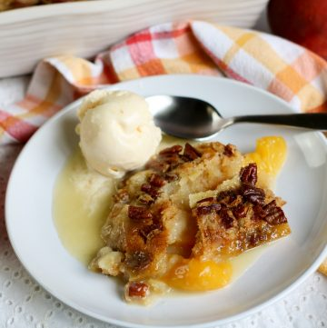 peach dump cake on white plate with vegan ice cream and orange and yellow checked napkin in back
