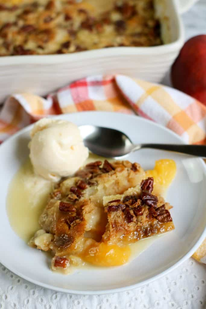 peach dump cake on white plate with vegan ice cream and orange and yellow checked napkin in back with white baking dish with cake inside