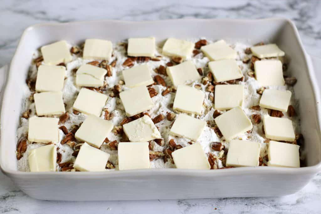 slices of vegan butter on top of dump cake