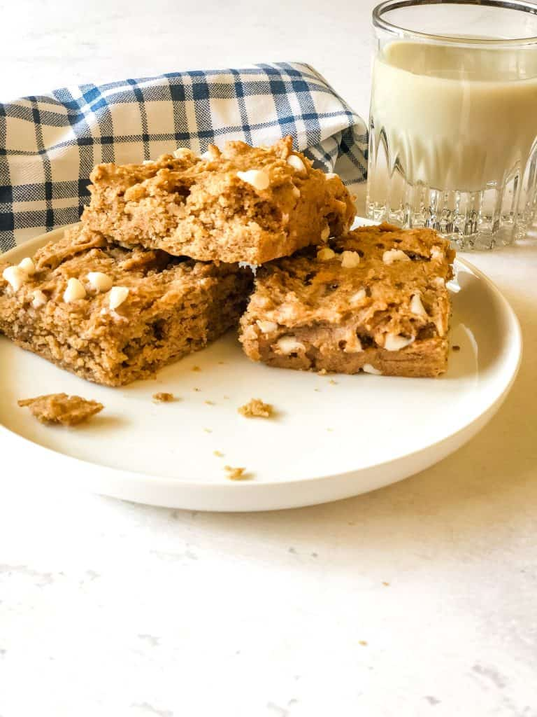 three blondies on plate with blue checked napkin and glass of oat milk in background