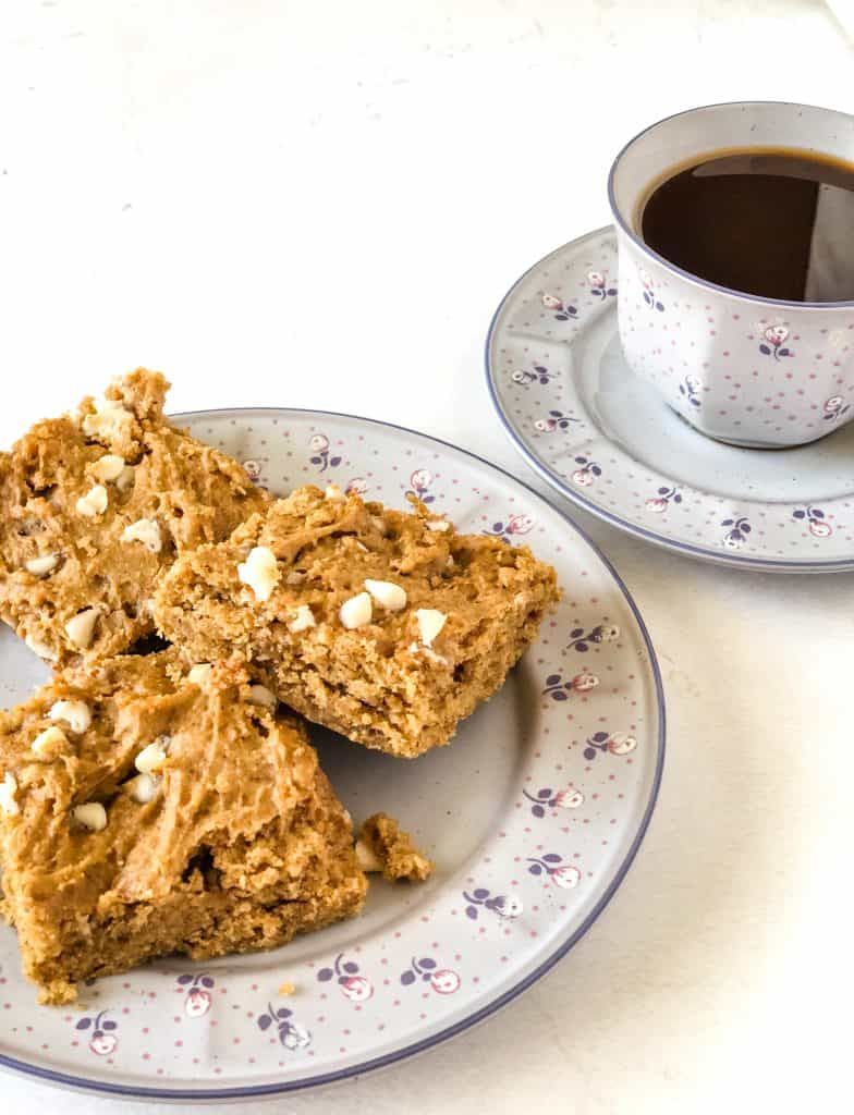 three blondies on purple flowered plate with cup of coffee in matching cup in background