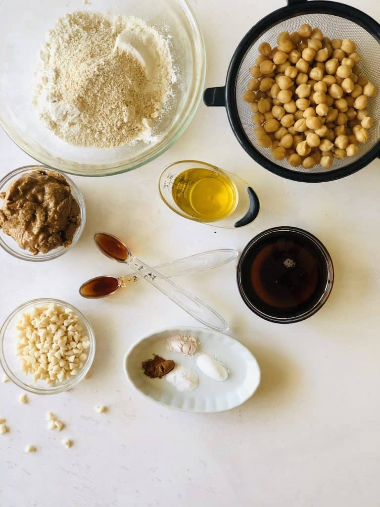 Ingredients needed for almond butter blondies including chickpeas, flour, almond butter, chocolate chips, vanilla, maple syrup, oil, spices