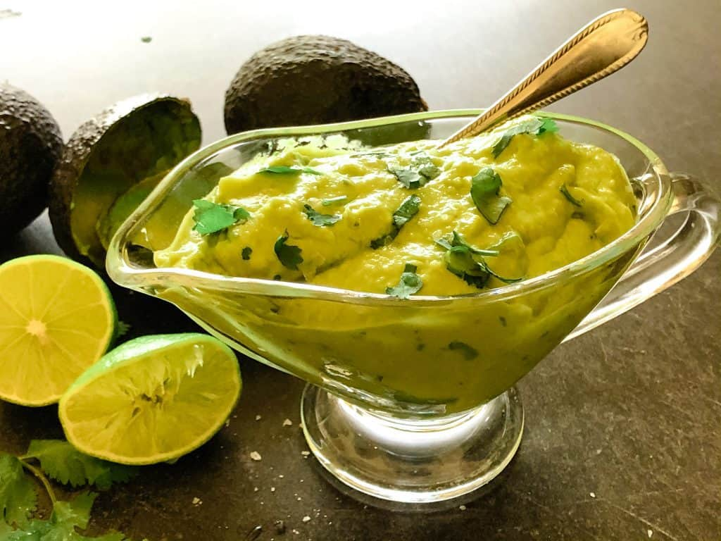 thick avocado sauce in glass gravy dish with limes and avocados in background