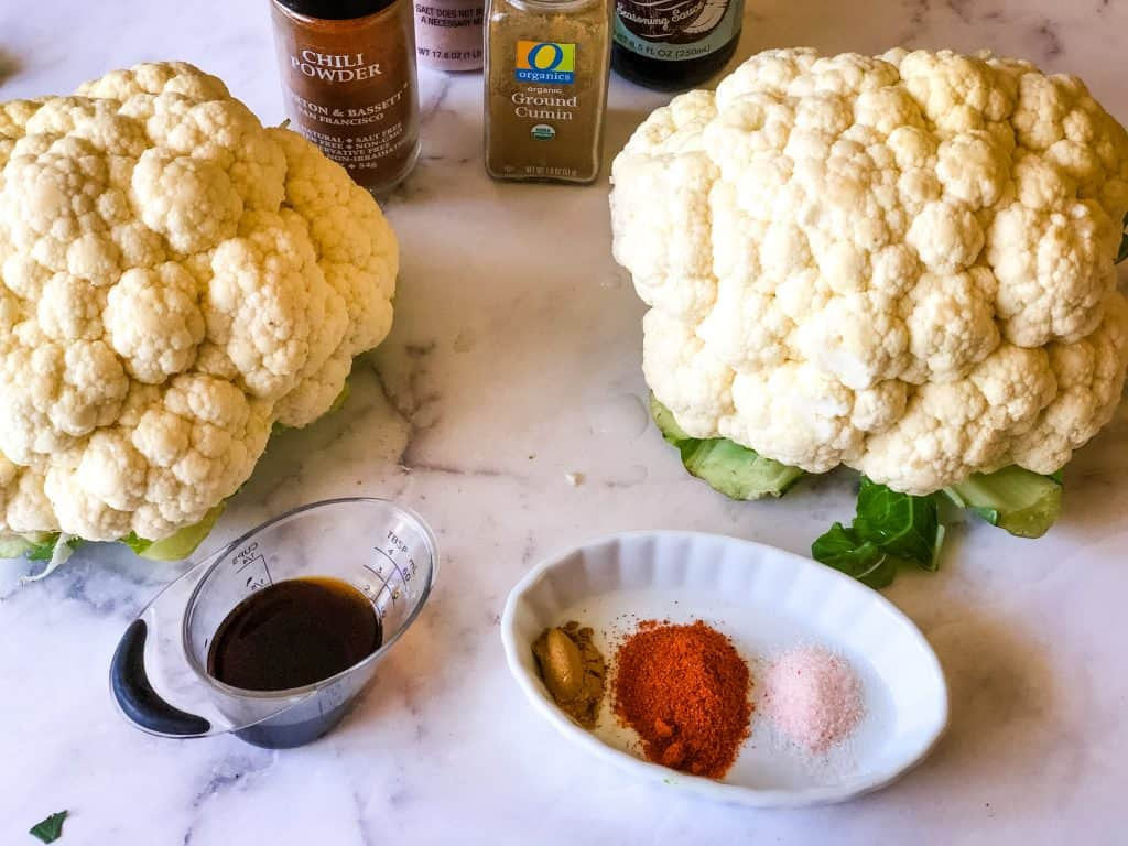 two heads of cauliflower, coconut aminos, and seasonings in white dish including salt, chili powder, and cumin