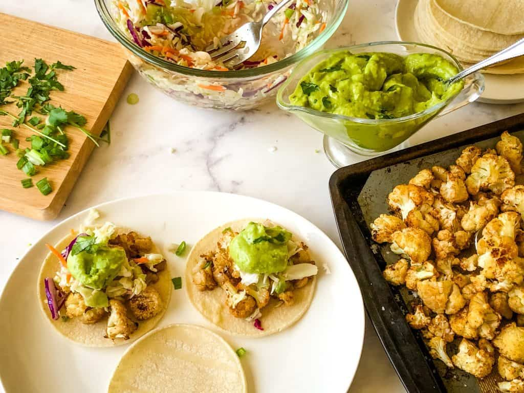 putting together the street tacos with white corn tortillas, roasted cauliflower bites, cilantro, coleslaw mixture, and creamy avocado sauce