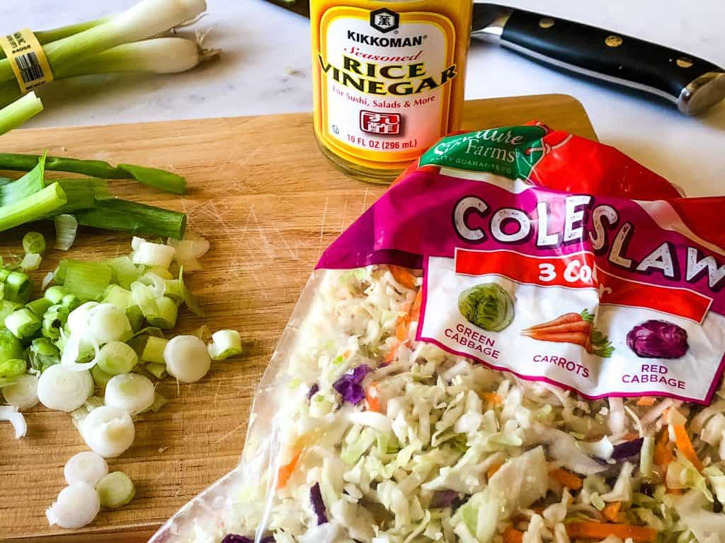 ingredients needed for the seasoned coleslaw including packaged coleslaw mix, sliced green onions, and seasoned rice vinegar