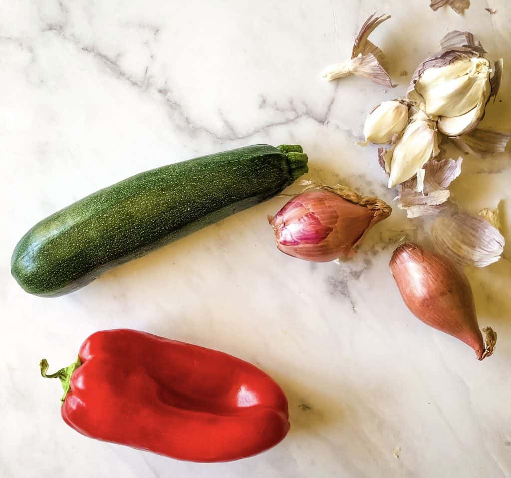 fresh ingredients needed for enchiladas including red bell pepper, zucchini, shallots, garlic
