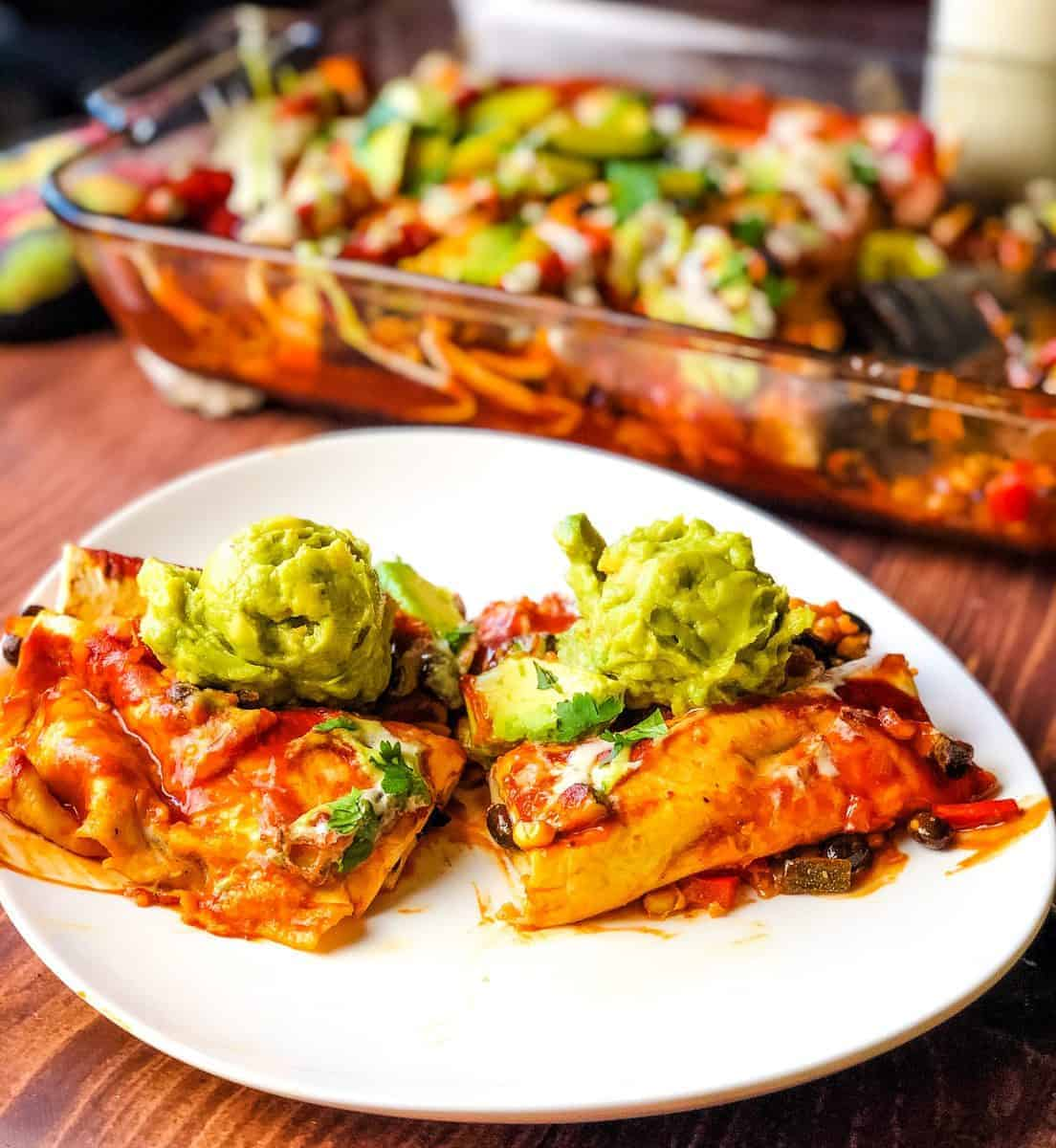 black bean enchiladas on white plate with casserole dish in background