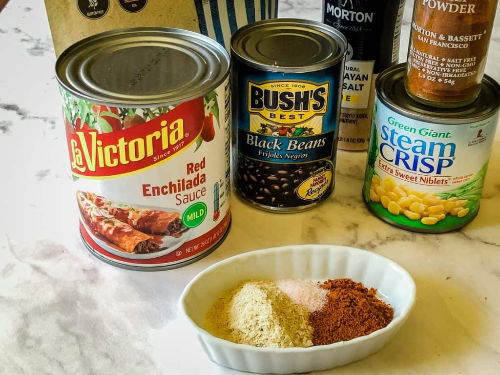 canned and dried Ingredients needed for enchiladas including enchilada sauce, black beans, nutritional yeast, corn, chili powder and salt