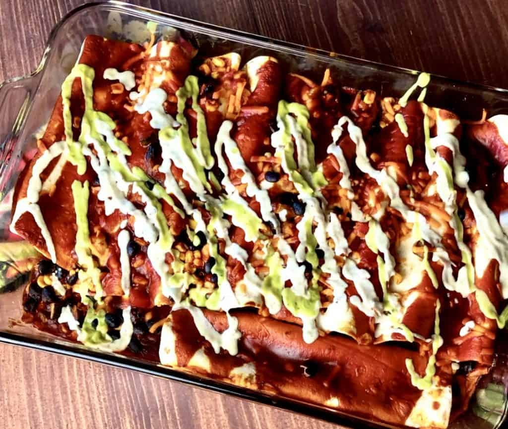 pan of black bean enchiladas with toppings