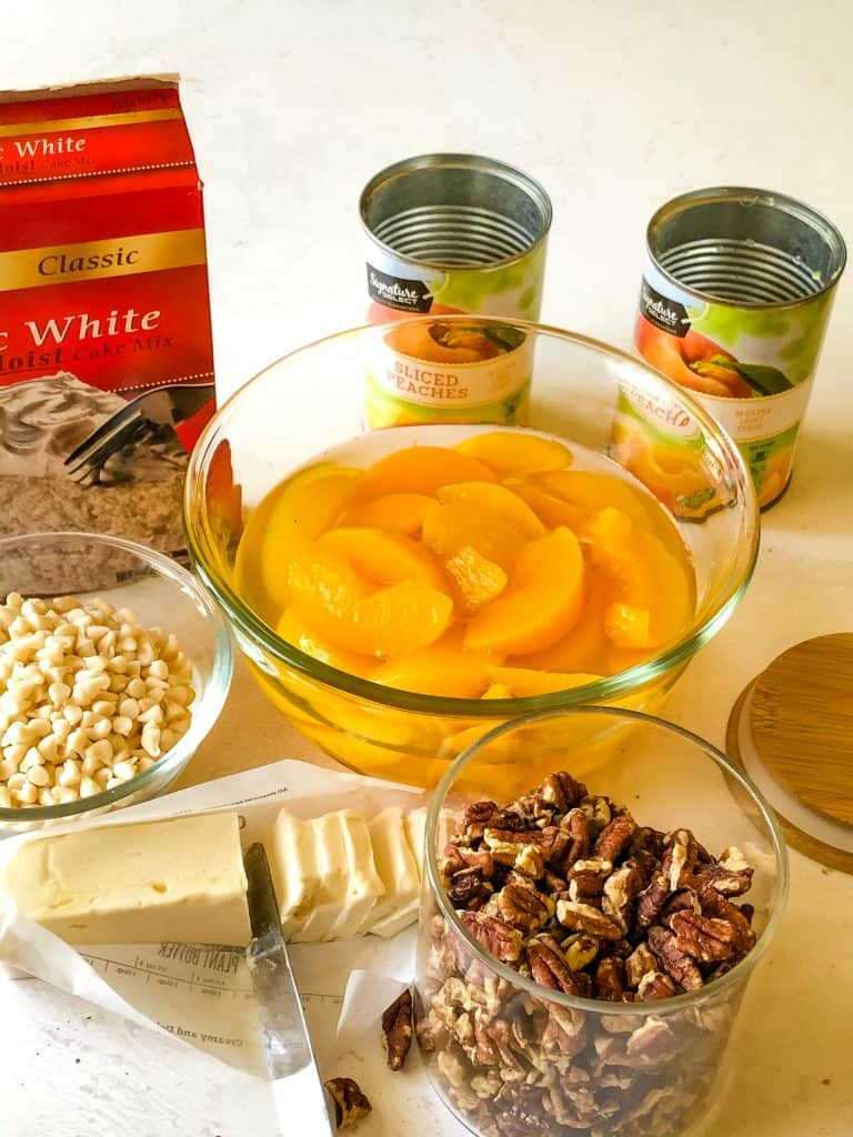 ingredients needed for peach dump cake including canned peaches, cake mix, vegan butter, pecans,
