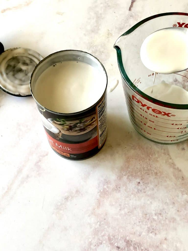 the cream from canned coconut milk being carefully spooned into a measuring cup