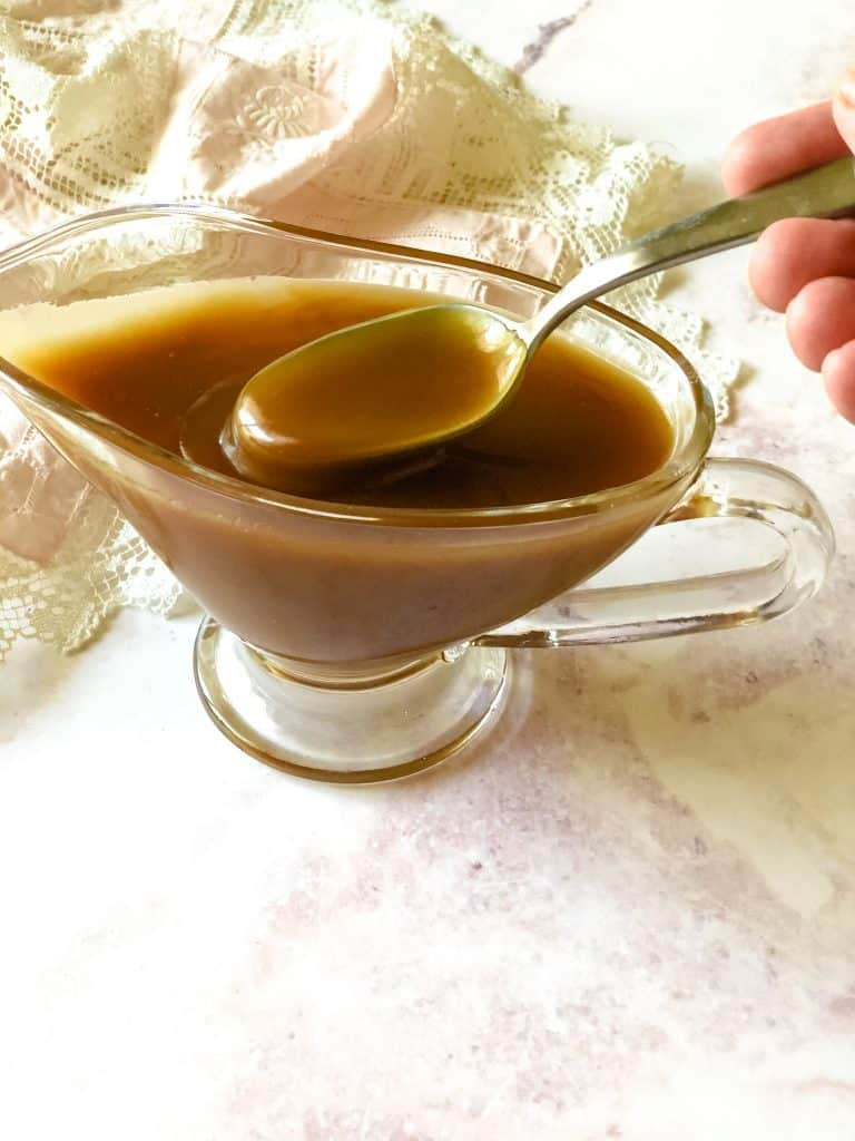 glass gravy boat filled with caramel sauce with spoon dipping some out