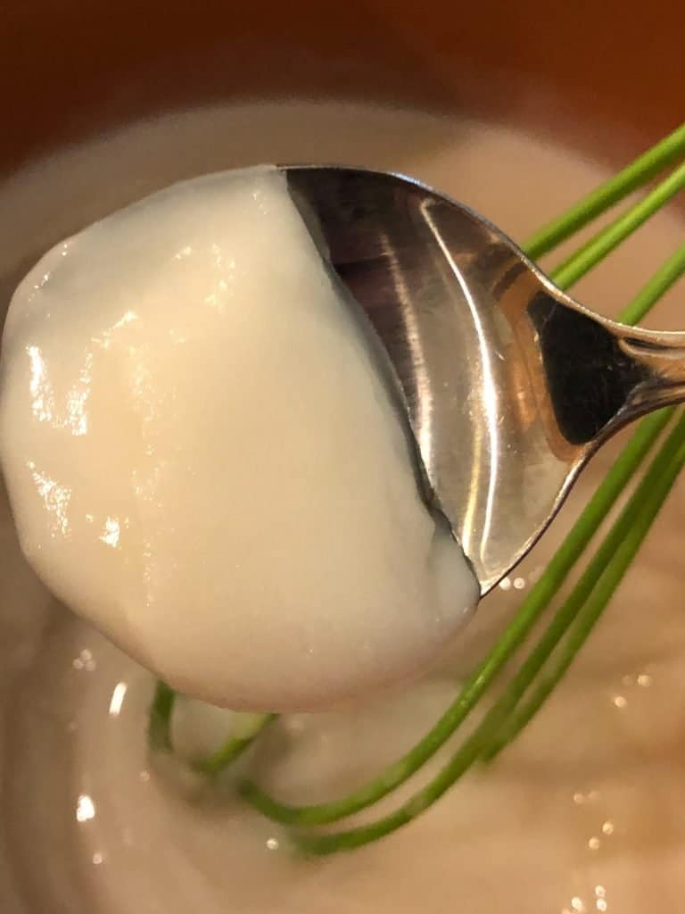 cooked and cooled coconut milk on spoon showing thickness